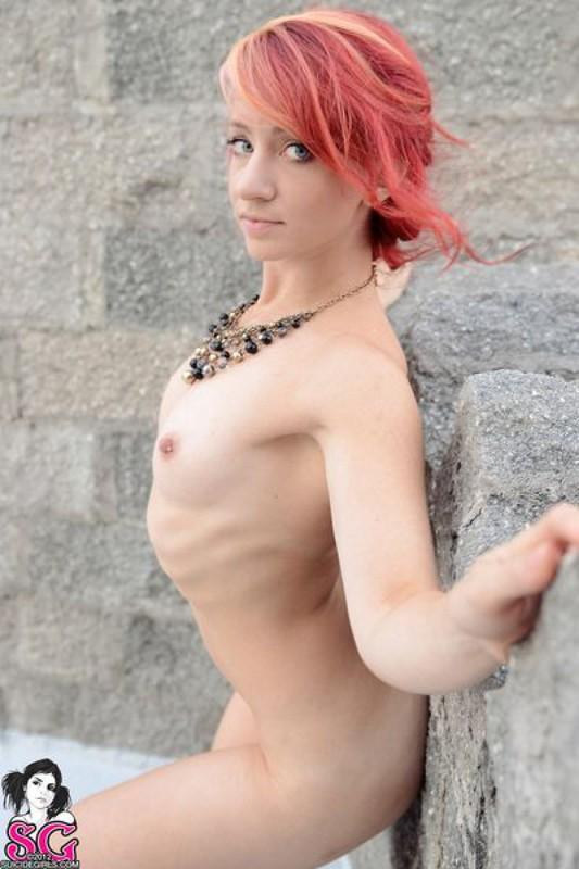 Милая давалка без одежды фотографируется около стен замка