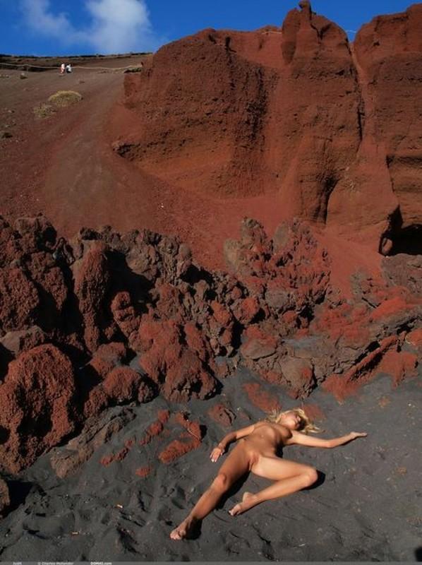 Обнаженная блондинка показывает себя на красных скалах