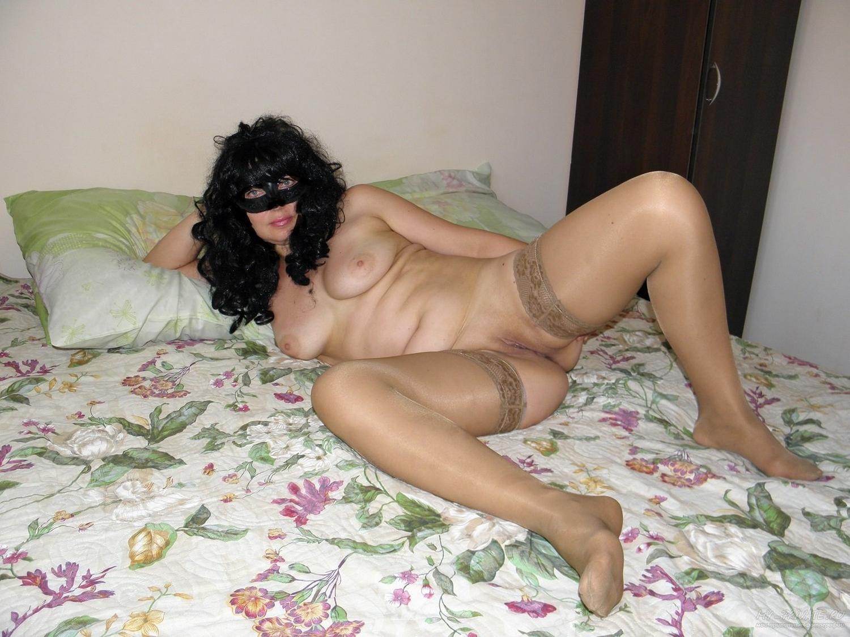 Брюнетка в маске на кровати демонстрирует письку