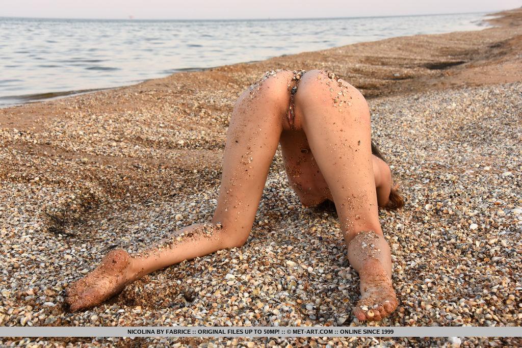Бритая фрау проветривает киску на морском берегу