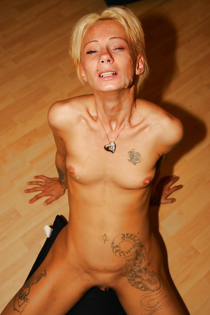 Татуированная шлюха целует фаллос чувака сидящего на козетке
