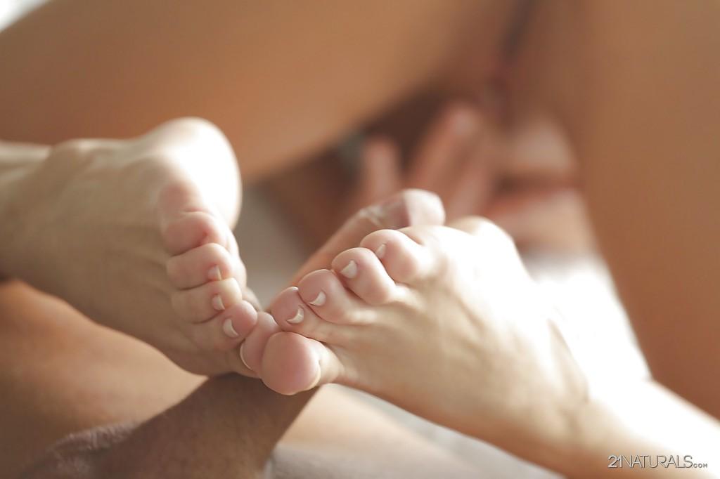 В постели голая деваха мастурбирует ступнями пенис