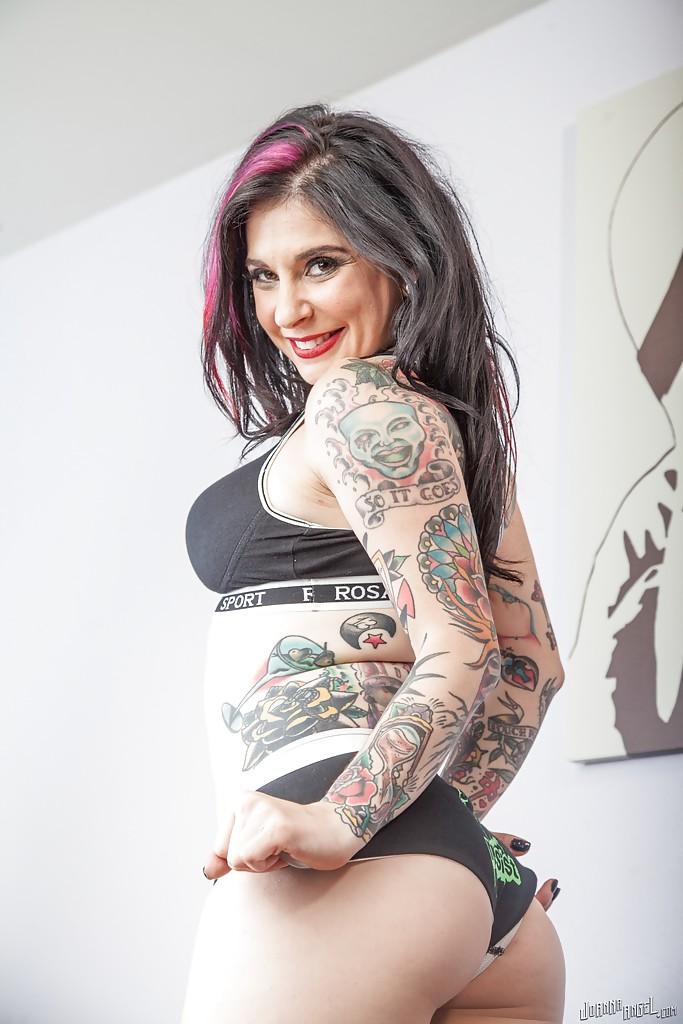 Татуированная мамка сексуально позирует на диване