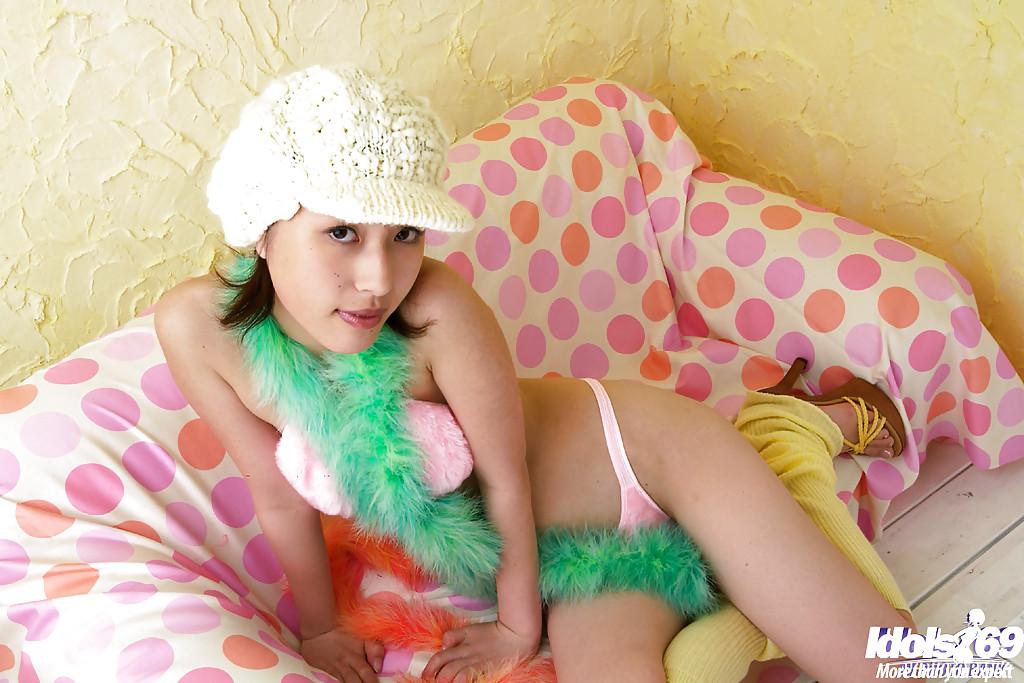 Азиатка в розовом белье позирует у себя в комнате