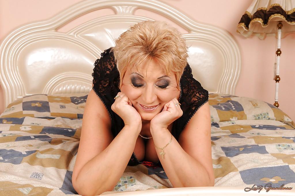 Сисястая бабушка разделась до чулков на кровати
