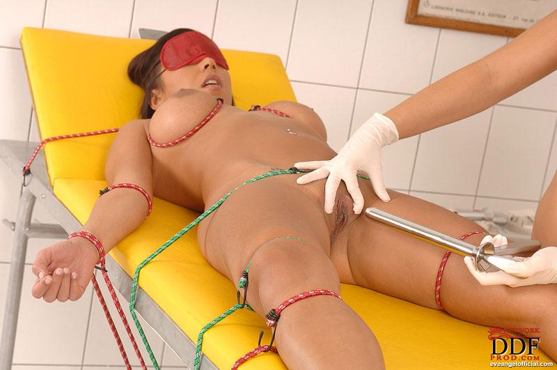 Гинеколог играет со связанной пациенткой металлическими инструментами