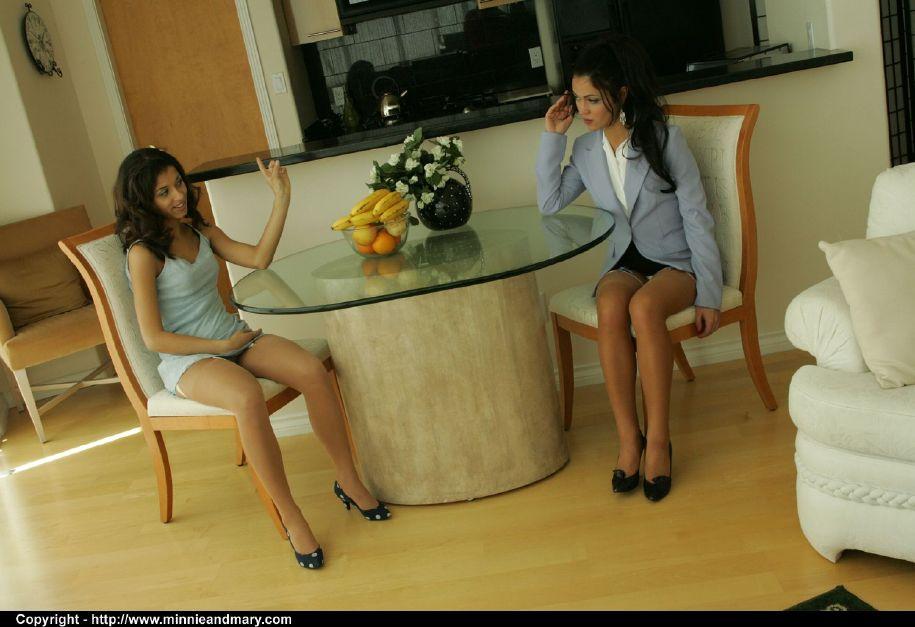 Возле стола лесбиянки раздевают друг дружку