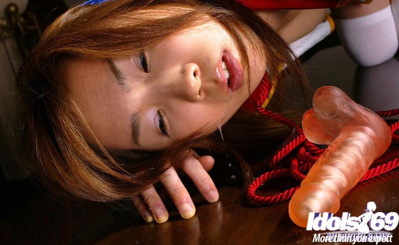 С самотыком во рту азиатка стоит на столе раком будучи связанной