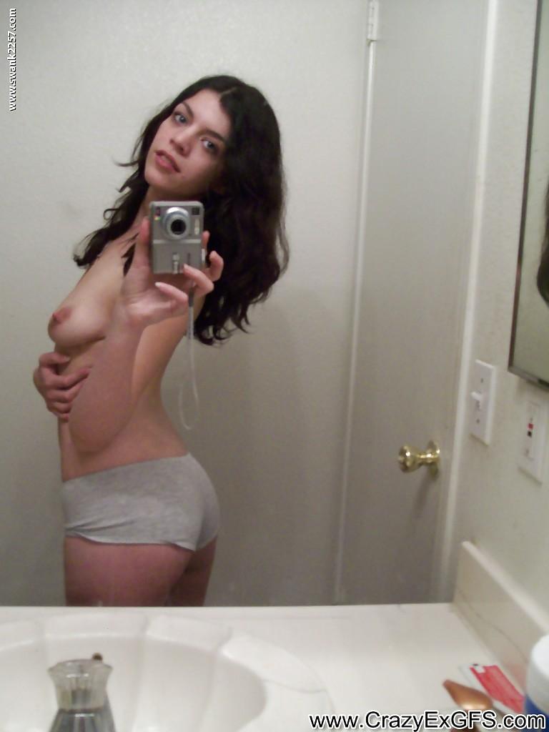 Темноволосая девка показывает перед зеркалом голая грудь