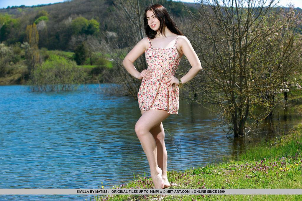На фоне реки нимфа выставляет напоказ тело