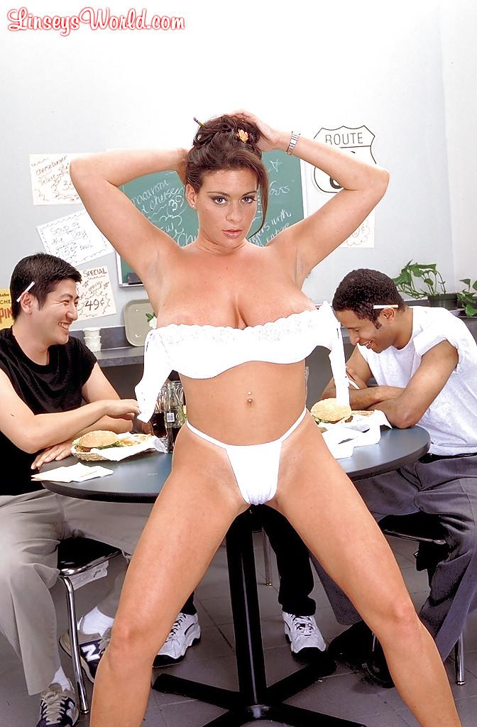 Официантка раздевается возле столика посетителей