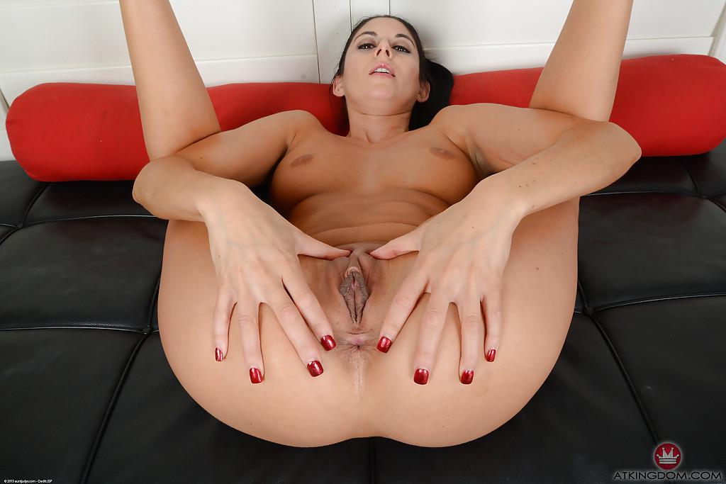 Девка на черном диванчике показывает аккуратную киску