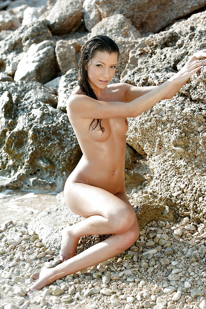 Обнаженная сучка позирует на каменистом берегу моря