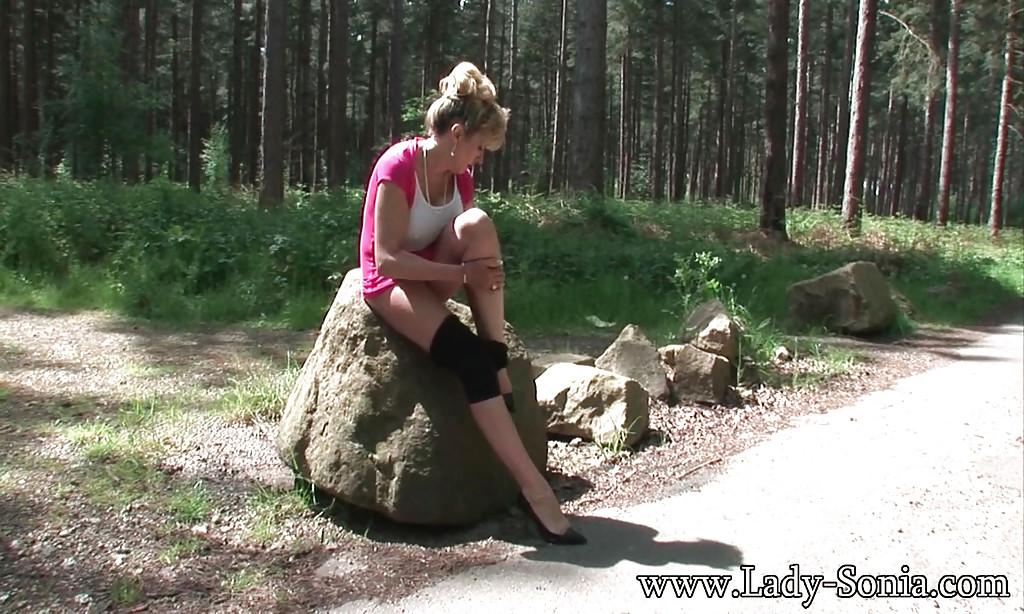 Сидя недалеко от камня взрослая блядь мастурбирует пилотку