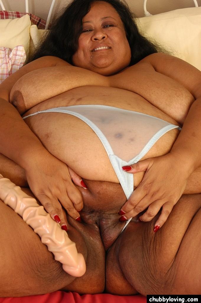 Безумно толстая негритоска в кровати шалит с толстым дилдо