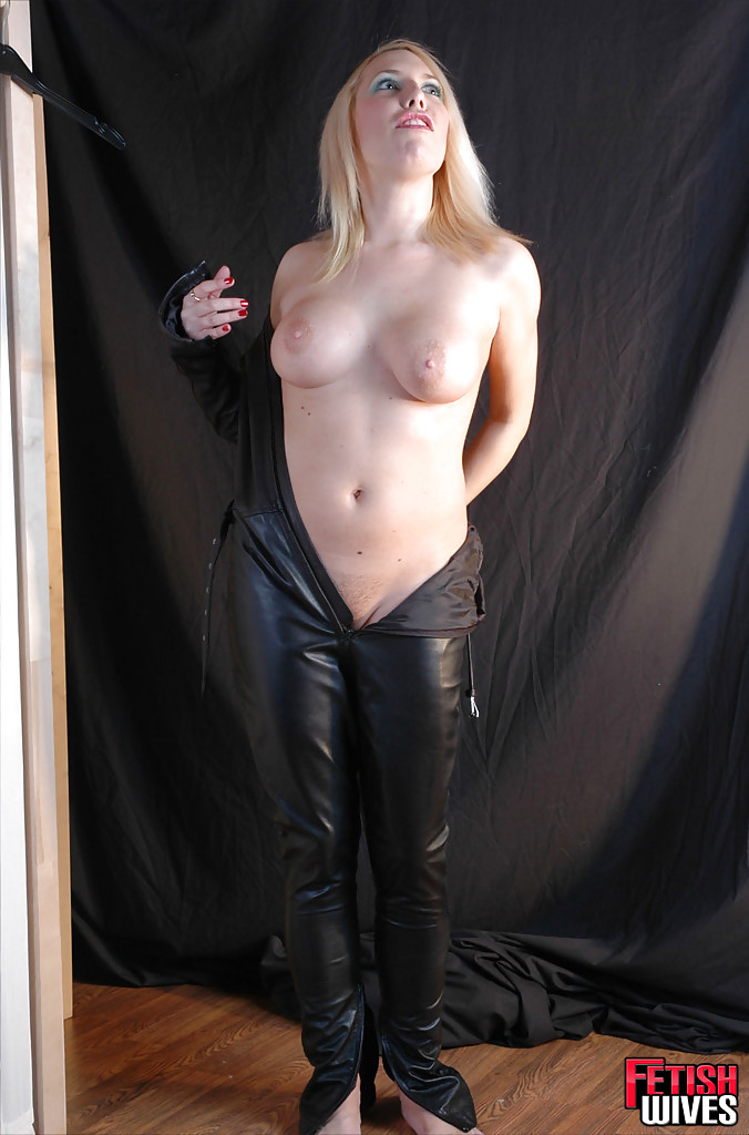 Блондинка надевает кожаный костюм на голое тело