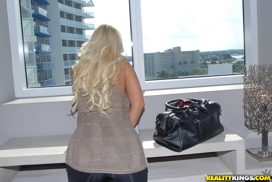 Блонда в сиреневом боди хвастается жопой в небоскребе