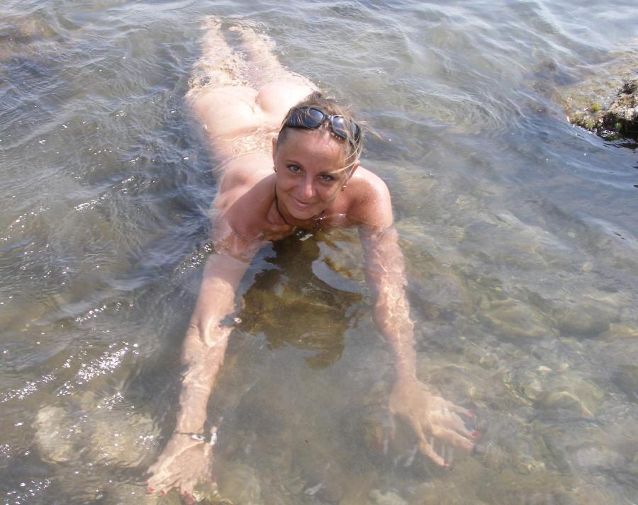 Зрелка в красных плавках балуется на песке