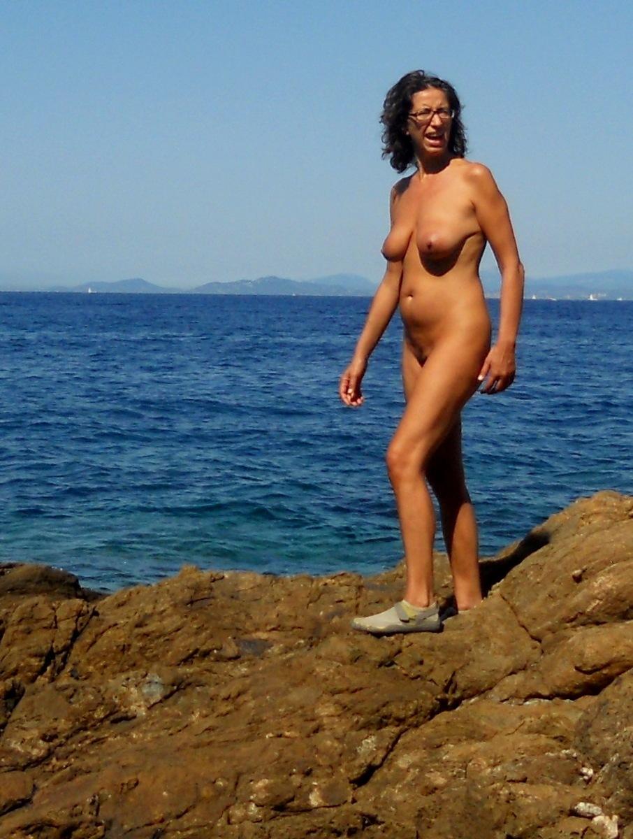 Голая зрелка отдыхает на пляже