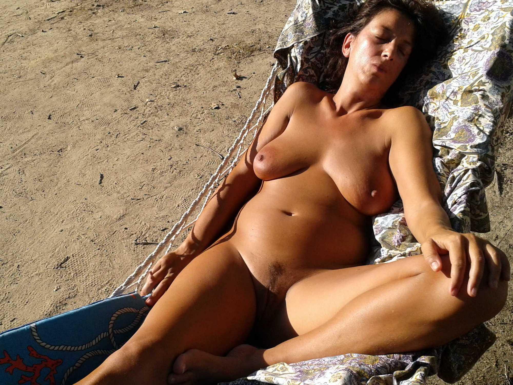 Голая милфа лежит на надувном матрасе под солнцем