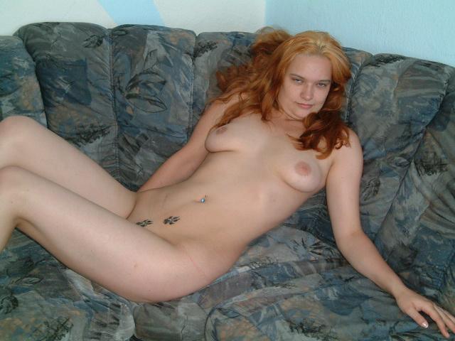 Рыженькая баба без трусов мастурбирует на диванчике