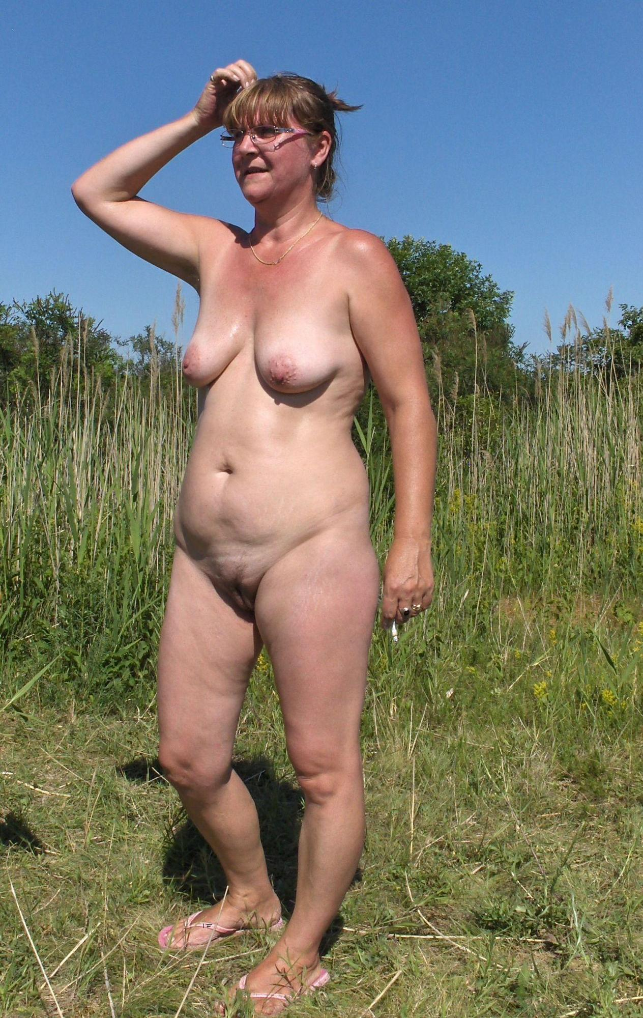 Сорокадевятилетняя барышня стоит в поле без трусиков