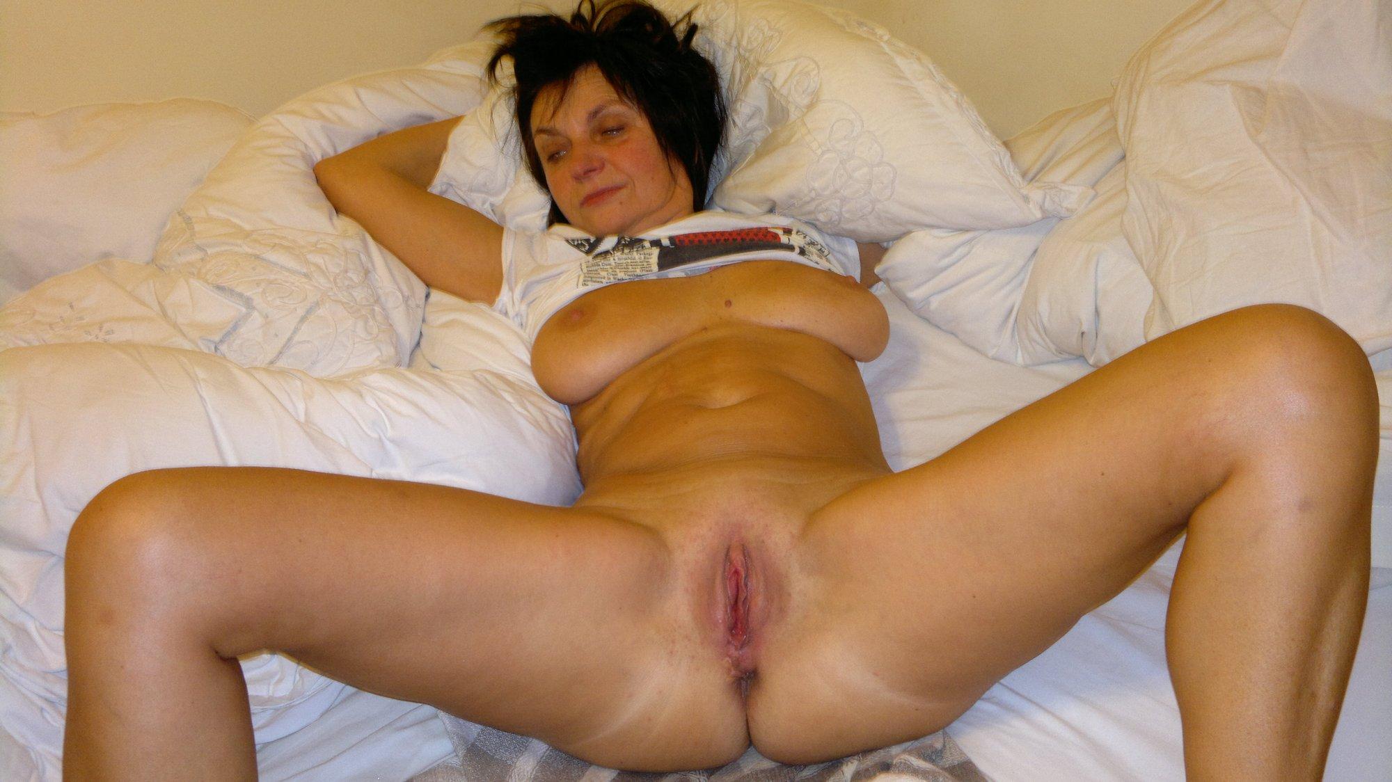 Лежа на кровати зрелка в чулках светит мандой
