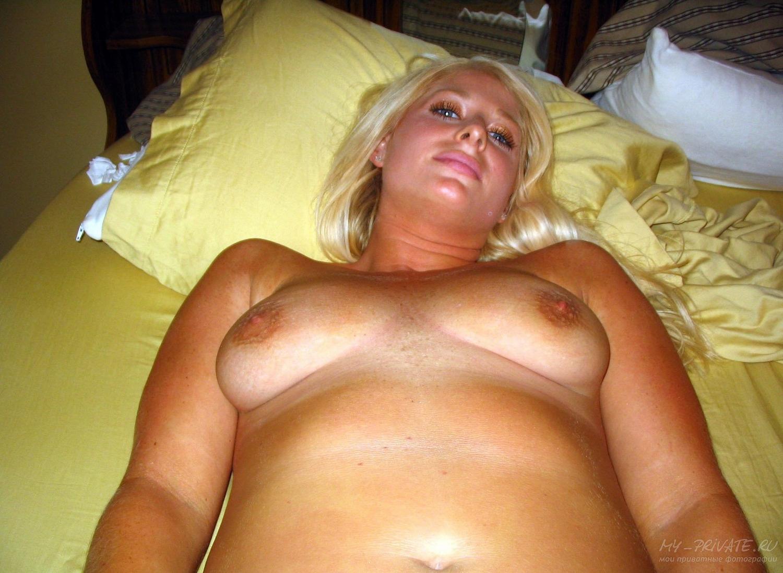 Лежа на постели блонда крупным планом показывает киску в трусиках