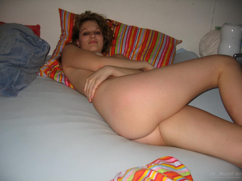 Обнаженная девушка валяется на постели перед сном