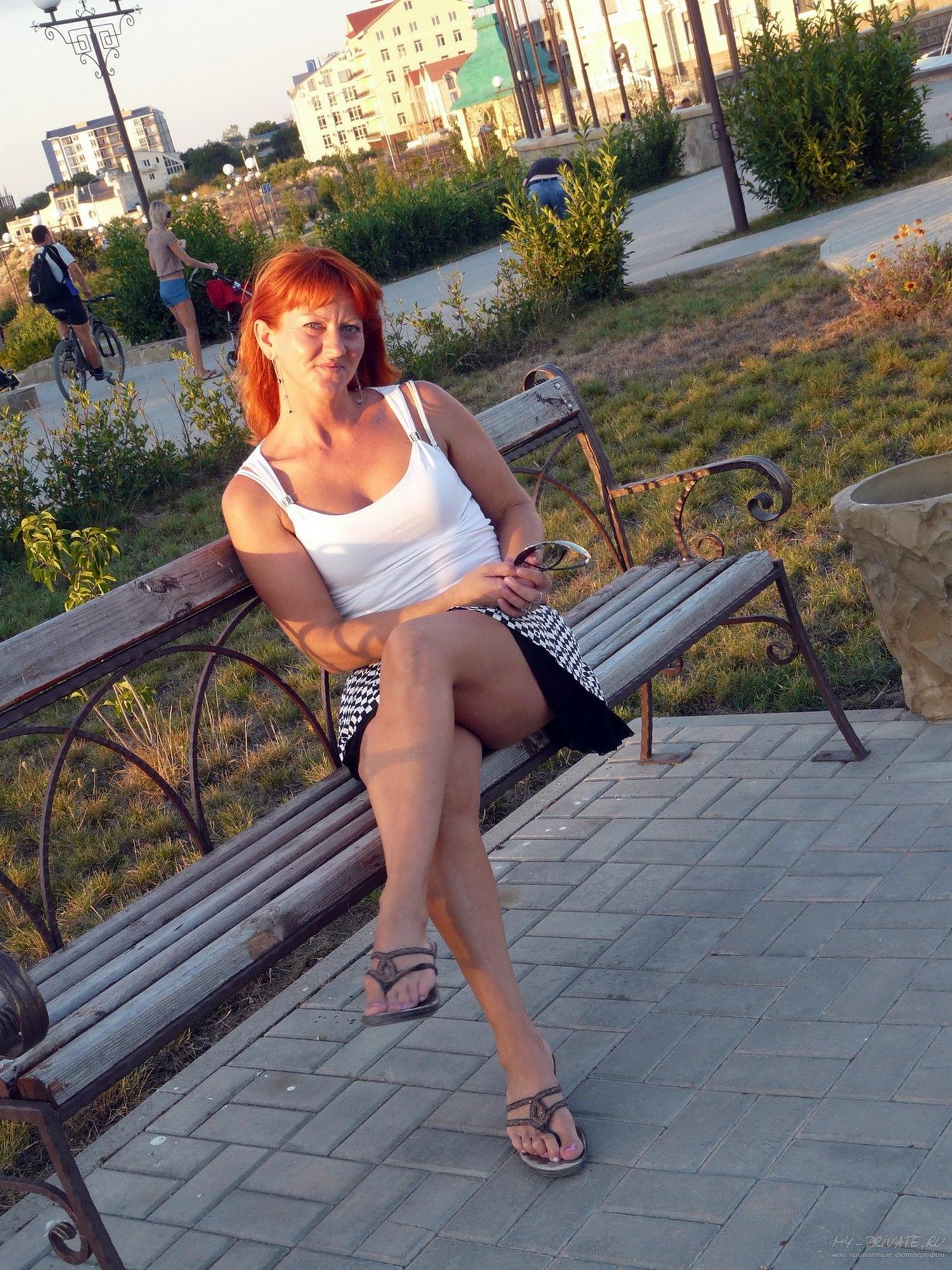 Рыженькая тетка на прогулке светит киску под юбочкой