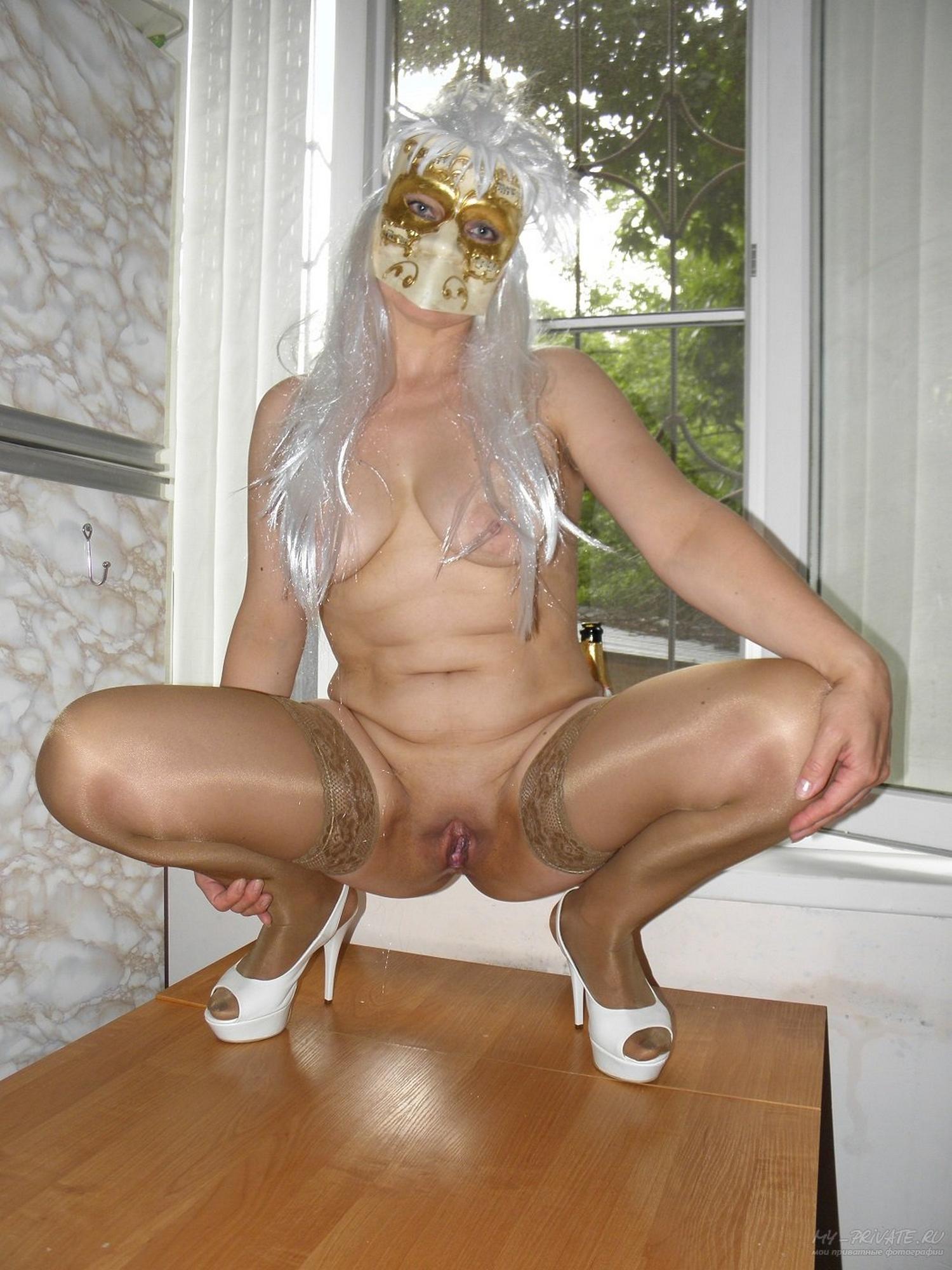 Нимфа в парике и маске показывает писю на столе