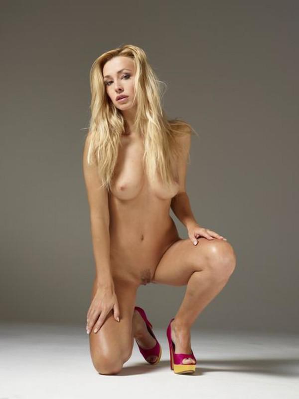 Привлекательная блондинка фотографируется в студии сидя на корточках