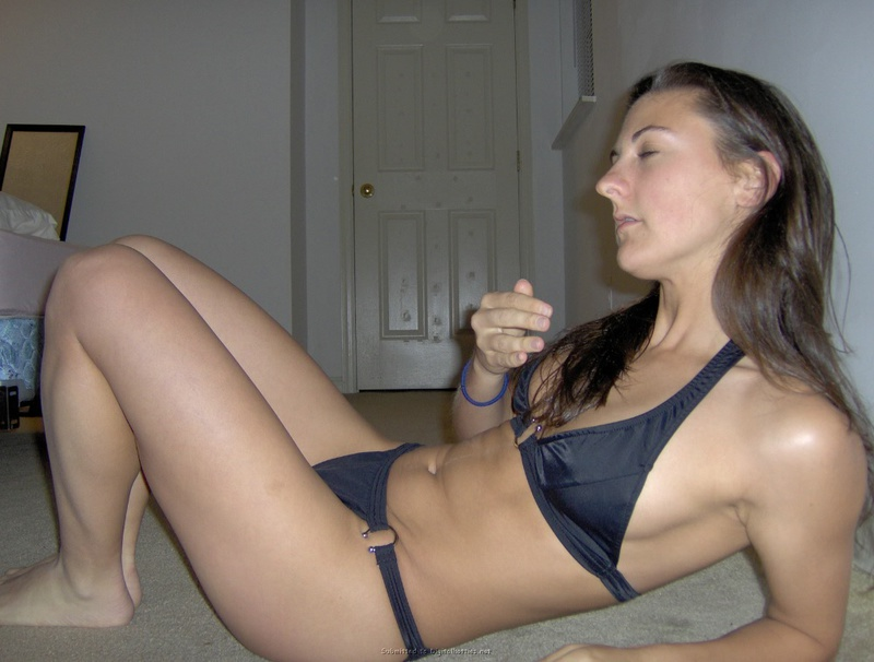 Стройная девушка позирует дома в новом купальнике
