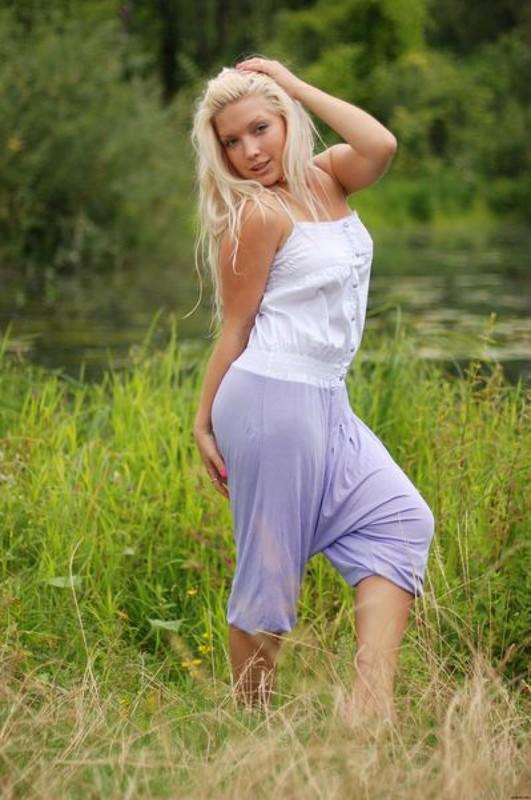 Сексуальная блондинка без одежды сидит на зеленой лужайке