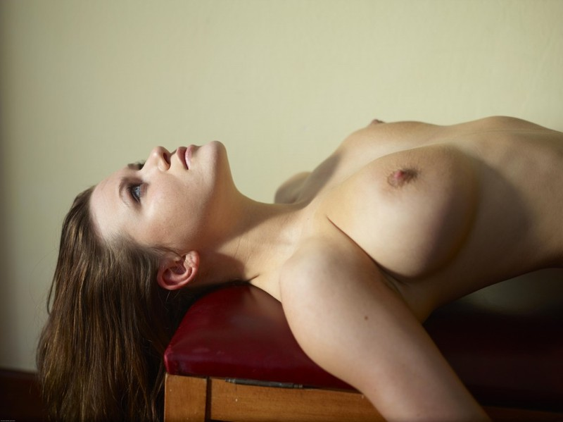 Обнаженная сучка лежит на красной сидушке