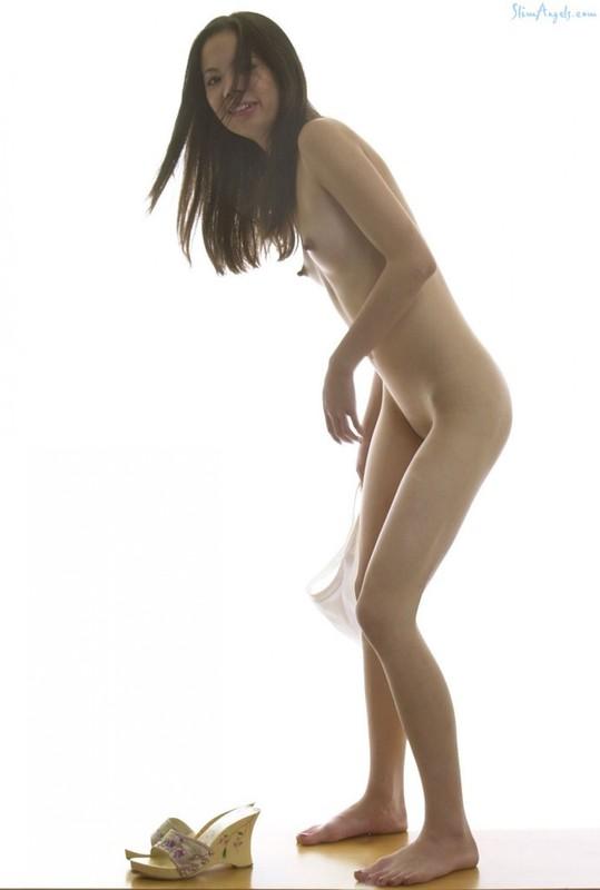 Худенькая азиаточка спускает бикини на белом фоне