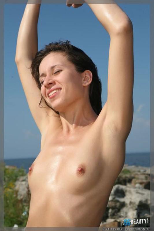 Симпатичная телка без одежды фотографируется на камнях на берегу моря