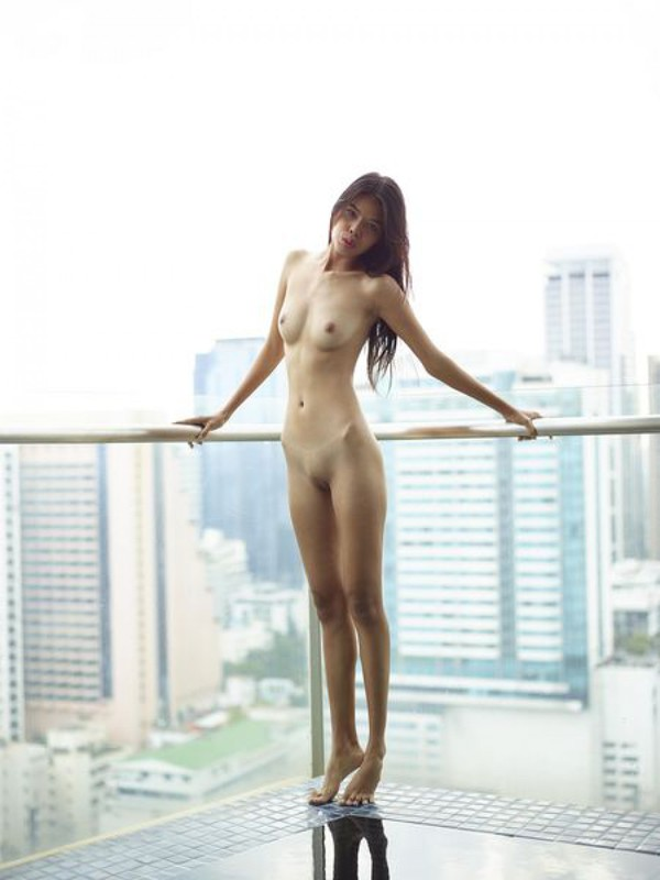 Голая и красивая блондинка позирует возле балкона