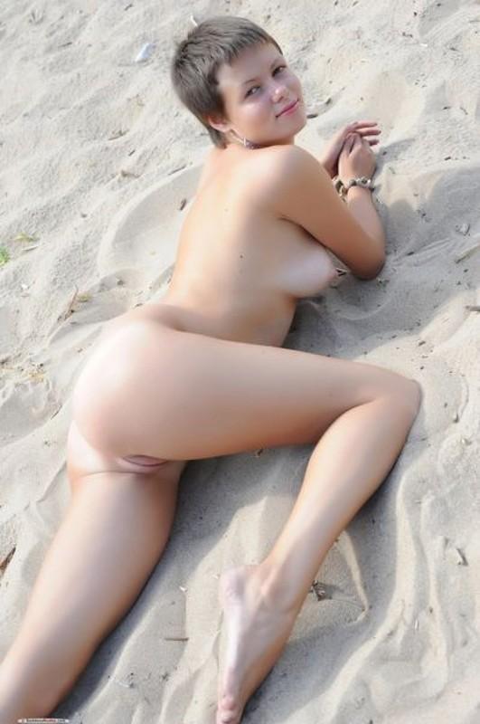 Коротко чистенькая девка без лифчика сидит на берегу моря секс фото