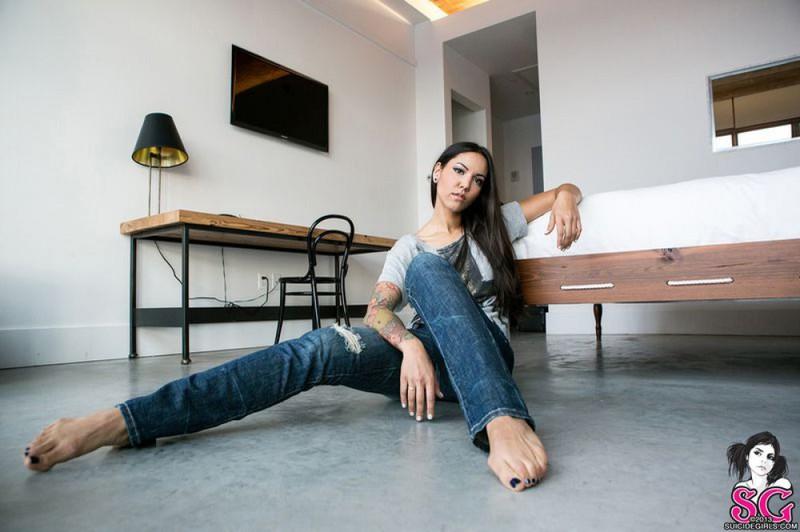 Татуированная темноволосая девка лежит на полу с голыми буферами