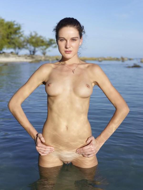 Стройная грешница голышом стоит на берегу океана
