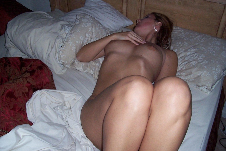 Молодая девка оголилась и массирует на кроватке мокрую вульву