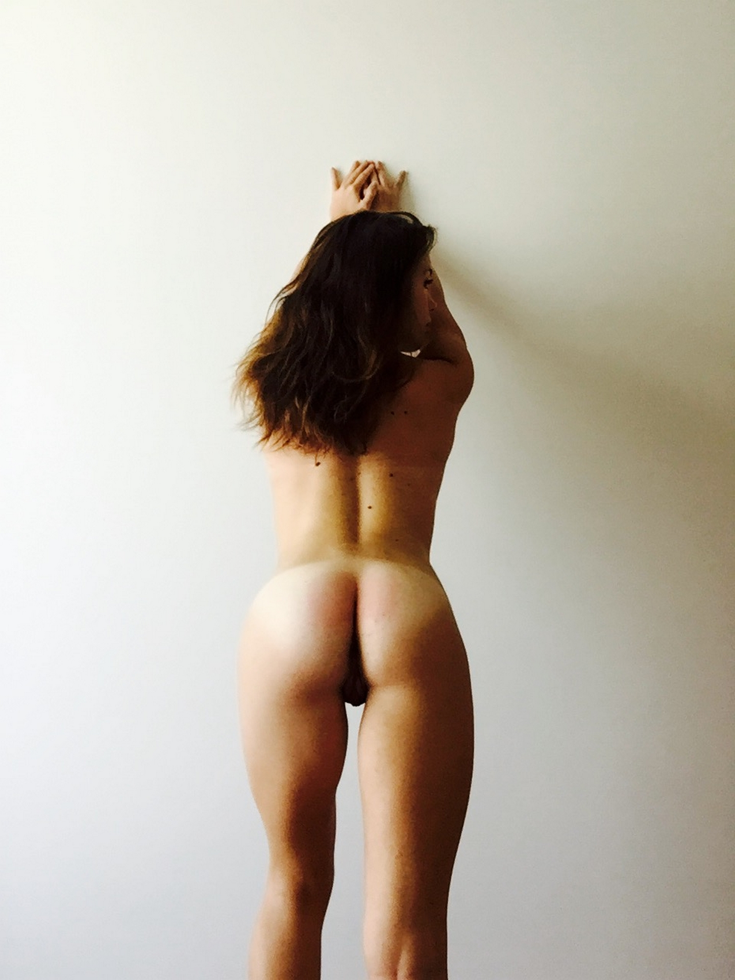 Загорелая спортсменка стоит у стены и хвастается стройным телом