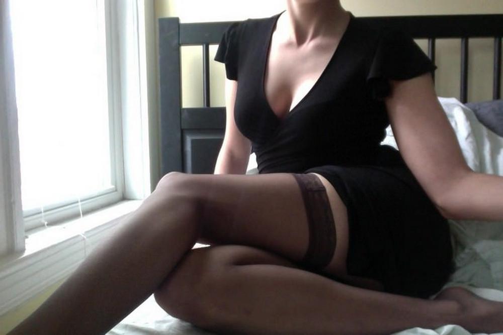 Дама в черном белье широко развела ноги и трогает киску пальцами