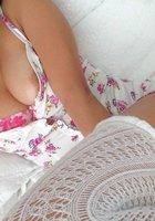 Девушка снимает цветное белье и позирует голой в постели около ноутбука 9 фотография