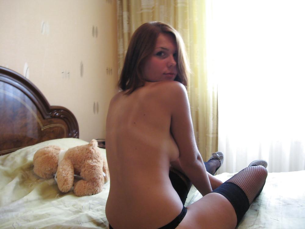 Барышня в чёрном белье сексуально делает селфи на двуспальной кроватки