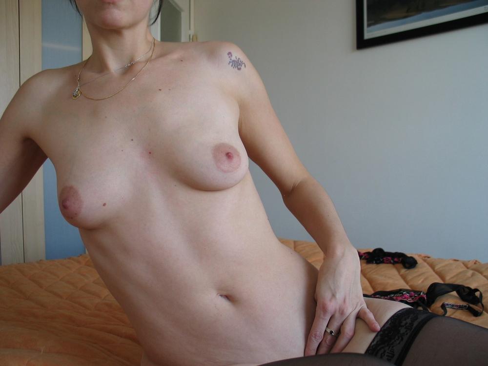 Модель с наколкой на плече сексуально фотографируется на лежанке