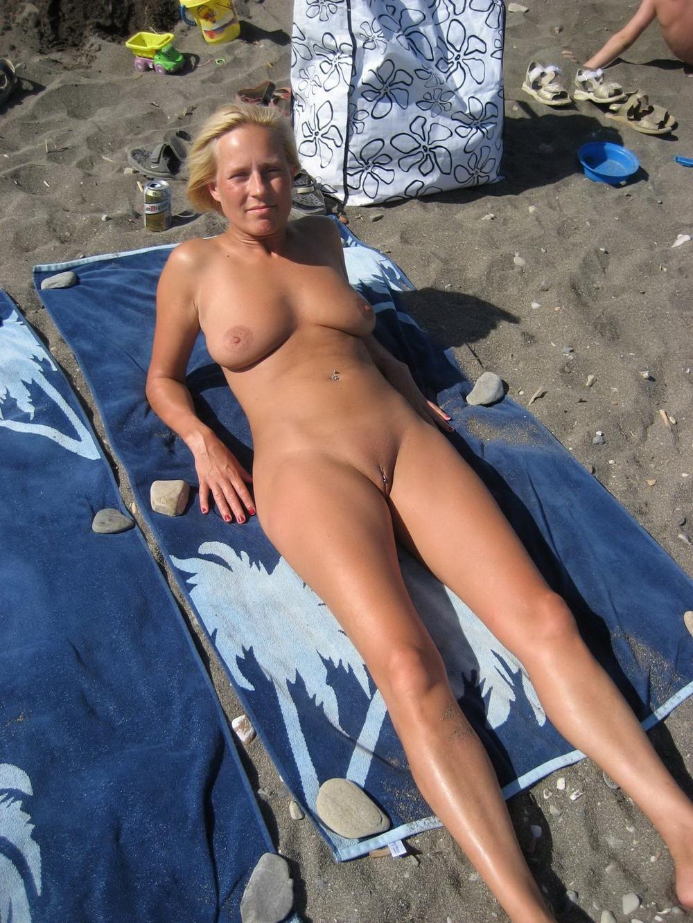 Блондинистая нудистка загорает на общественном песке без купальника
