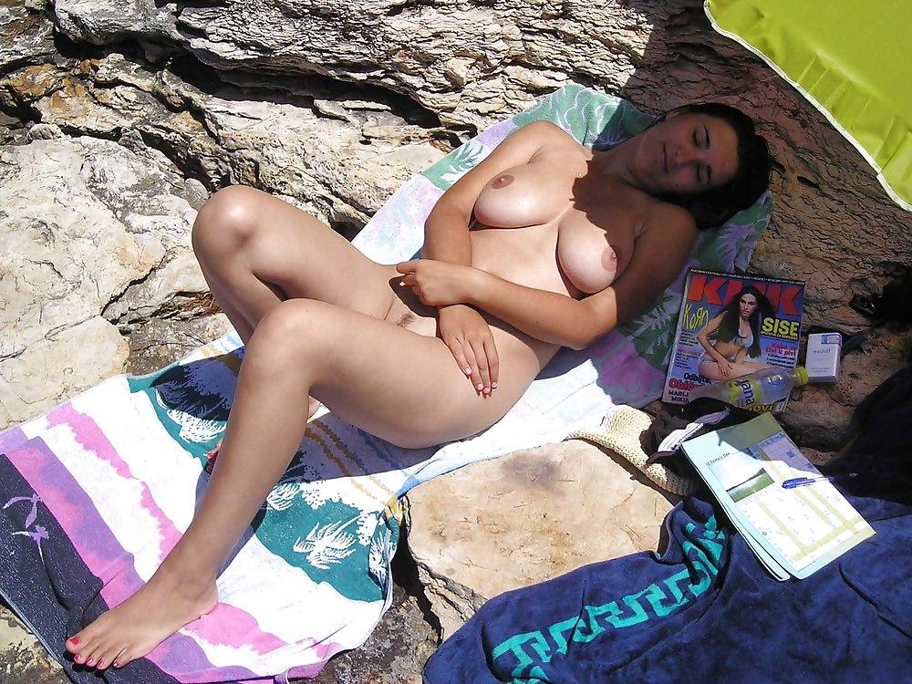 Большегрудая чика с интимной стрижкой отдыхает на берегу моря