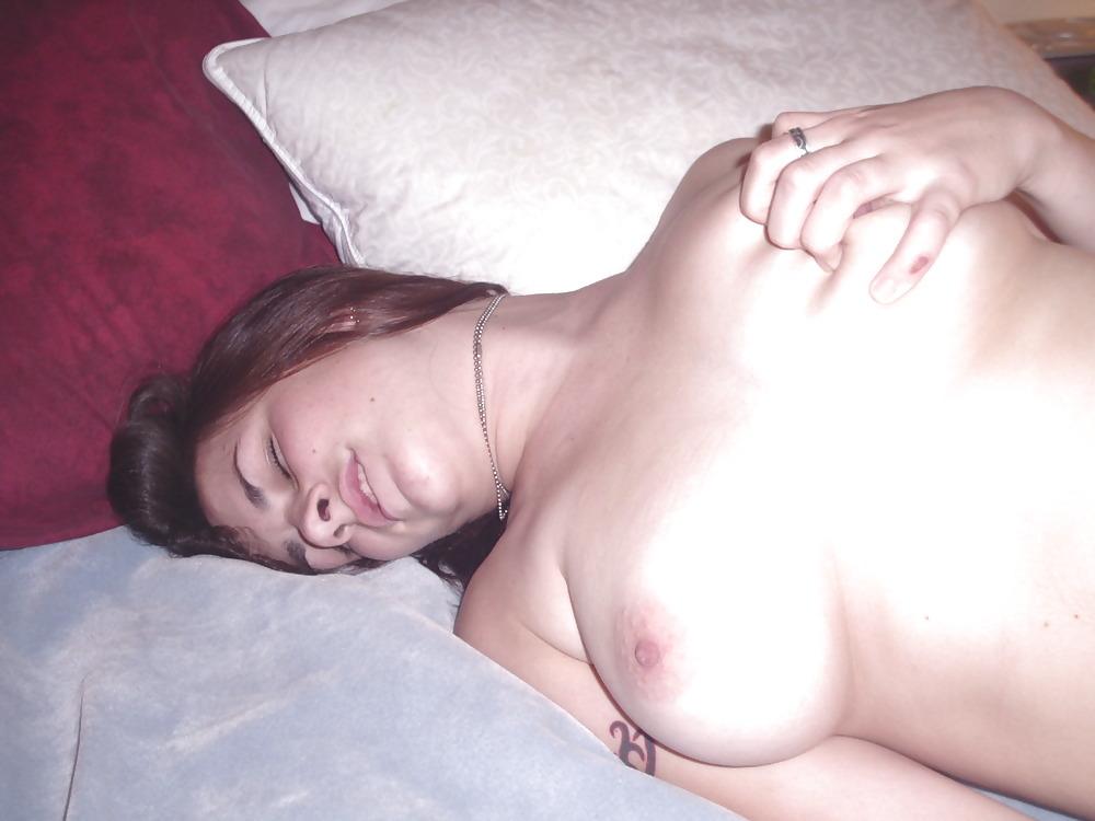 Голая баба с тату на правом плече светит титьками на кровати